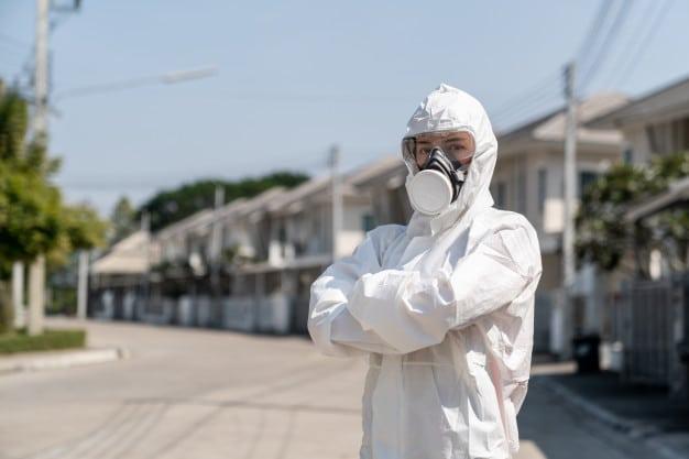 Pracownik w okmbinezonie ochronnym - ozonowanie